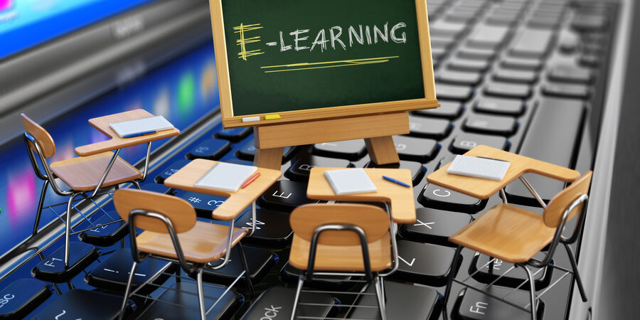 E-learning concept. Schooldesk and chalkboard on the laptop keyboard. 3d